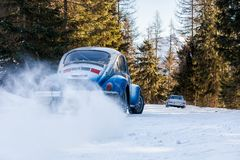 Vintage racing car drifting on classic rally snow covert road. Vintage racing car drifting on a classic rally on snow covert road on mountain Planai  in Austria Stock Photo