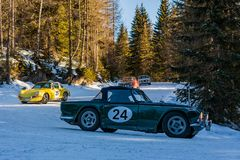 Vintage racing car driving classic rally on snow covert road Royalty Free Stock Photos