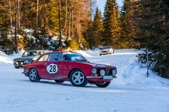 Vintage racing cars driving classic rally on snow covert road. Vintage racing cars driving a classic rally on snow covert road on mountain Planai  in Austria Royalty Free Stock Image