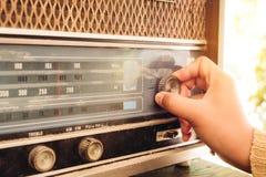 Vintage radio receiver. Retro lifestyle - Woman hand adjusting the button vintage radio receiver for listen music or news - vintage color tone effect Royalty Free Stock Photos