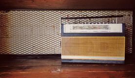 Vintage radio receiver. On the wooden shelf with white brick wall and wire mesh in background Royalty Free Stock Photography