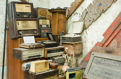 Vintage radio receptor and some other antiques and old electronic devices inside antique shop Stock Image