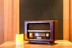 Vintage radio set. Old-fashioned wooden radio set and a yellow candle on a table Royalty Free Stock Images