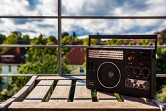 Vintage radio. On a wooden chair, outdoors Royalty Free Stock Photo