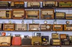 Vintage Radios and clocks. Old clocks and radios aligned in row side by side royalty free stock photography