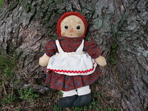 Vintage Raggedy Ann sitting by tree Stock Photos