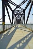 Vintage railway bridge repurposed as a walkway across the Ohio r. Iver. Rising steel beams create shaddows on the walkway royalty free stock image