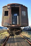 Vintage railway carriage. In poor condition with missing glass in window but still on railway line with factories to left and right, blue sky background royalty free stock photography