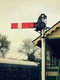 Vintage railway stop signal with signal box and train in the background. At the East Anglian Railway Museum, Chappel and Wakes Colne Station, UK Stock Photography