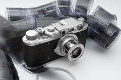 Vintage rangefinder camera in black and white film. Vintage rangefinder camera over black and white film rolls Royalty Free Stock Photos