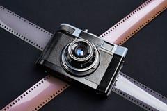 Vintage rangefinder camera and photographic films. On black Royalty Free Stock Image