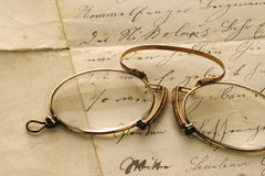Vintage Reading. Closeup of a vintage pince-nez lying on an old handwritten letter royalty free stock image