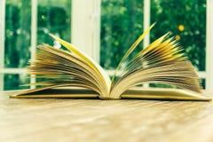 Vintage reading book near white window Stock Photo