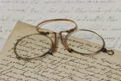 Vintage Reading. Closeup of vintage glasses lying on different old handwritten sheets of writing paper stock photo