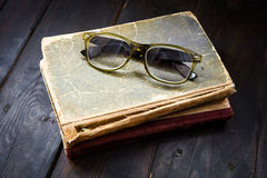 Vintage reading glasses on the books stack Stock Images