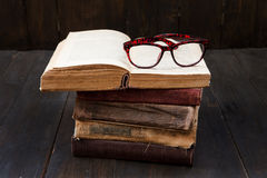 Vintage reading glasses on the books stack Stock Photos