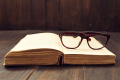 Vintage reading glasses on the open book Royalty Free Stock Photos