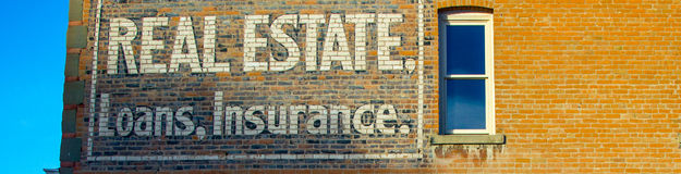 Vintage Real Estate, Loans and Insurance sign. Old Real Estate, Loans and Insurance sign on red brick building Royalty Free Stock Photos