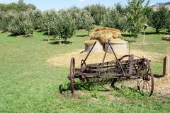 Vintage Reaper and Bales of Hay. An old rusted reaper and bales of hay at an apple orchard Royalty Free Stock Image