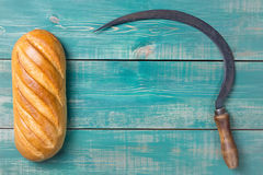 Vintage reaper hook sickle and bread on green wooden background.  Royalty Free Stock Photo