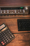 Vintage receiver and calculator on a wooden background. Vintage receiver and a calculator on a wooden background Stock Photography