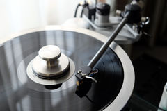 Vintage record player with graphite tonearm closeup view. Graphite tonearm of vintage turntable with LP record close up view Royalty Free Stock Photo