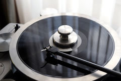 Vintage record player with tonearm closeup view. Graphite tonearm of vintage turntable with LP record close up view Stock Image