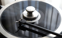 Vintage record player with tonearm closeup view. Graphite tonearm of vintage turntable with LP record close up view Royalty Free Stock Image