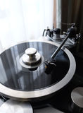 Vintage record player with tonearm closeup view. Graphite tonearm of vintage turntable with LP record close up view Royalty Free Stock Photo