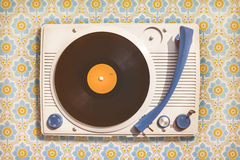 Vintage record player on top of flower wallpaper. Retro styled image of an old record player on top of flower wallpaper stock photography