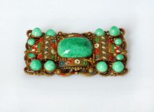 Vintage rectangular brooch with green stones. Historic beautiful enamelled brooch from brass with thirteen round natural stones named chrysopraze Royalty Free Stock Photography