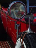 Vintage Red Auto. Close-up showing headlight, mirror and spare tire Stock Image