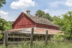 Vintage Red Barn in Ohio. An old red barn, faded from its former glory, stands among growing trees and brush in the Ohio countryside royalty free stock photography