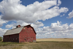 Vintage red barn on the prairies. Vintage barn on the prairies under a cloudy blue sky Stock Photos