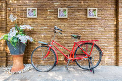Vintage red bicycle against sandstone brick wall with decoration Royalty Free Stock Photo