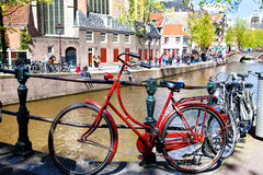 Vintage red bicycle near a Canal in Amsterdam Stock Photos