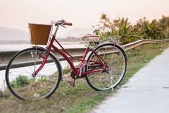 Vintage red bicycle beside river road Royalty Free Stock Images