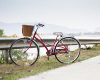 Vintage red bicycle beside river road Stock Photography