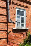 Drain or rain pipe on house. Vintage red brick wall with drain pipe and white window Royalty Free Stock Image