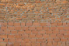 Vintage red brick wall. The bricks are lit by the rising sun. Vintage red brick wall. The wall is made of bricks of different sizes, both whole and broken. The royalty free stock photos