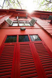 Vintage red building with wooden shutters. From bottom to top view against sunny summer sky background Stock Images