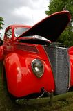 Vintage red car. With an open hood, on green grass Stock Photos