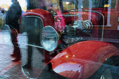 Vintage red car with reflection in the window of the city Stock Photo