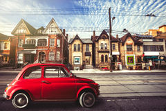 Vintage red car in the urban street. Toronto. Ancient old car parked on the street with houses in the background. Location: Toronto, Canada. Houses with sloping royalty free stock photos