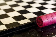 Vintage Red Checkers and Checker Board. A low perspective of a very old hand made checker board game with red checkers royalty free stock photos