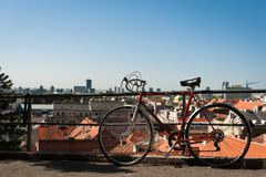 Vintage red city bicycle locked to the metal fence with view over Zagreb. Old red road bicycle. Royalty Free Stock Photo