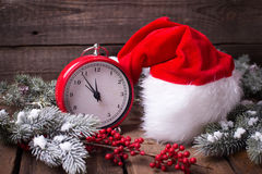 Vintage red clock, Santa hat , branches fur tree and red berrie. S on aged wooden background. Selective focus stock photography