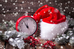 Vintage red clock, Santa hat , branches fur tree and red berrie. S on aged wooden background. Selective focus. Drawn snow royalty free stock photo