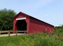 Vintage red covered bridge accross a river Royalty Free Stock Image