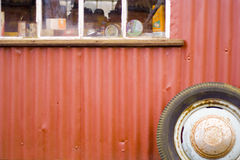 Vintage Red Garage. Old corrugated iron vehicle workshop with vintage car wheel and car care products in window Royalty Free Stock Photos